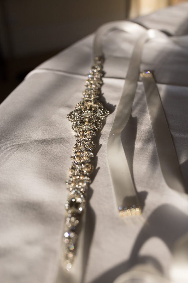 bride's diamante belt sparkles in the winter sunshine photographed at the Elvetham