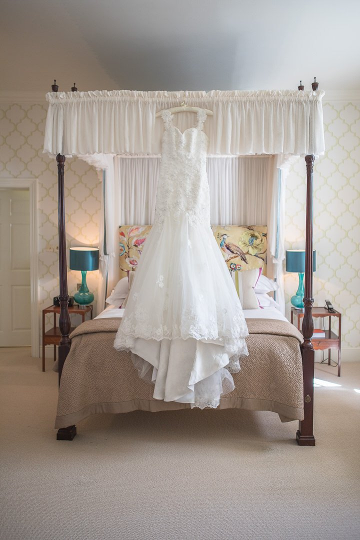 beautiful wedding dress hangs from the four poster bed at the Vineyard Hotel near Newbury