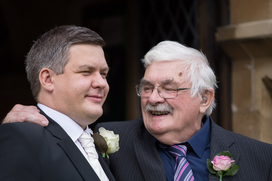 proud dad looks at his son the groom at St Leonards church in Woodcote in Berkshire