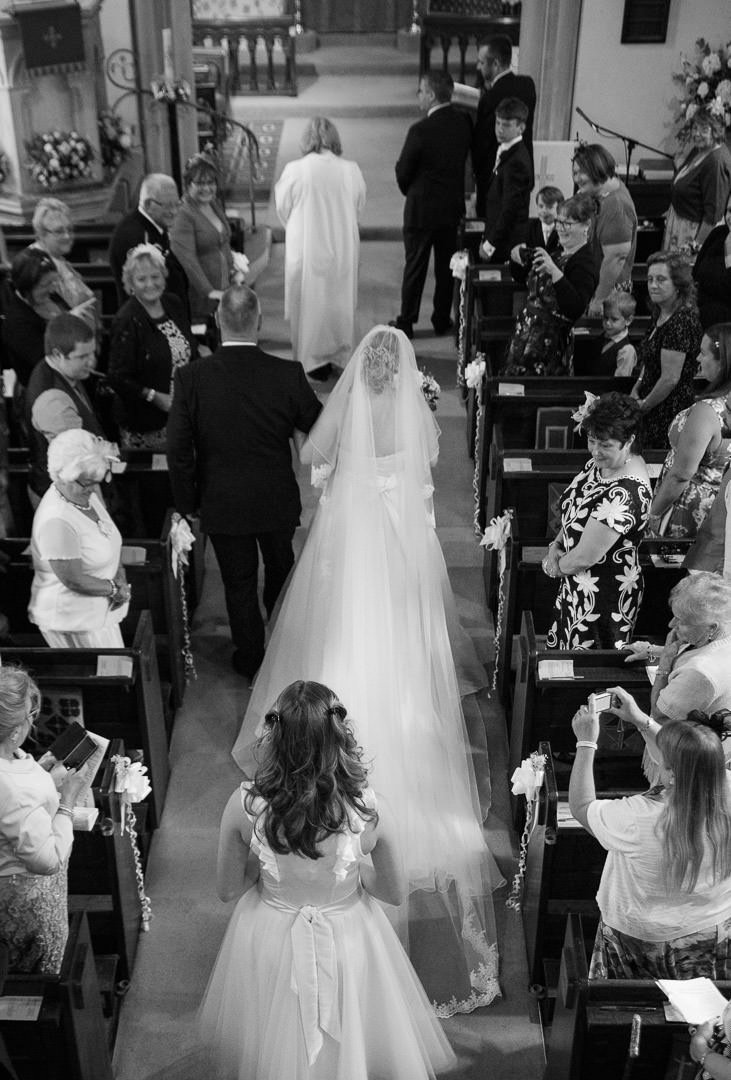 Bride walks down the aisle at St Leonard's church in Woodcote in Berkshire