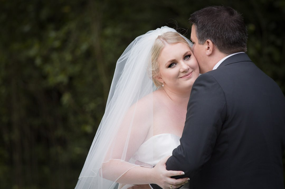 Groom kisses the bride at Badgemore Park in Berkshire