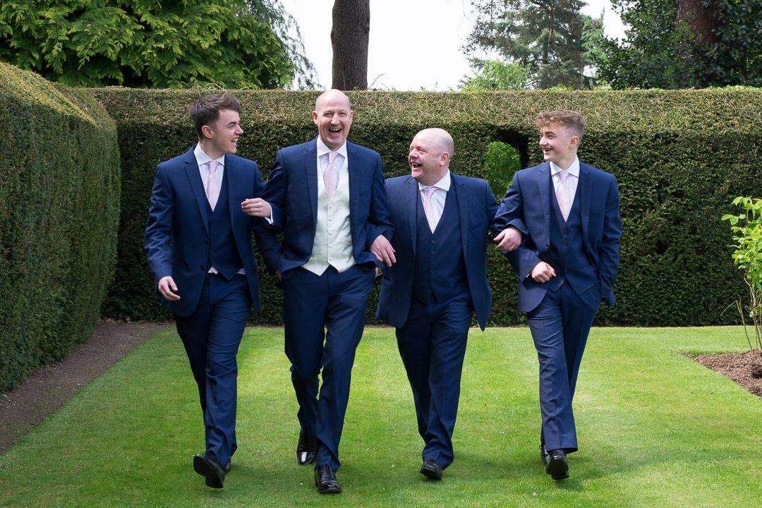 Groom and groomsmen walk along lawn at Barnett Hill Hotel