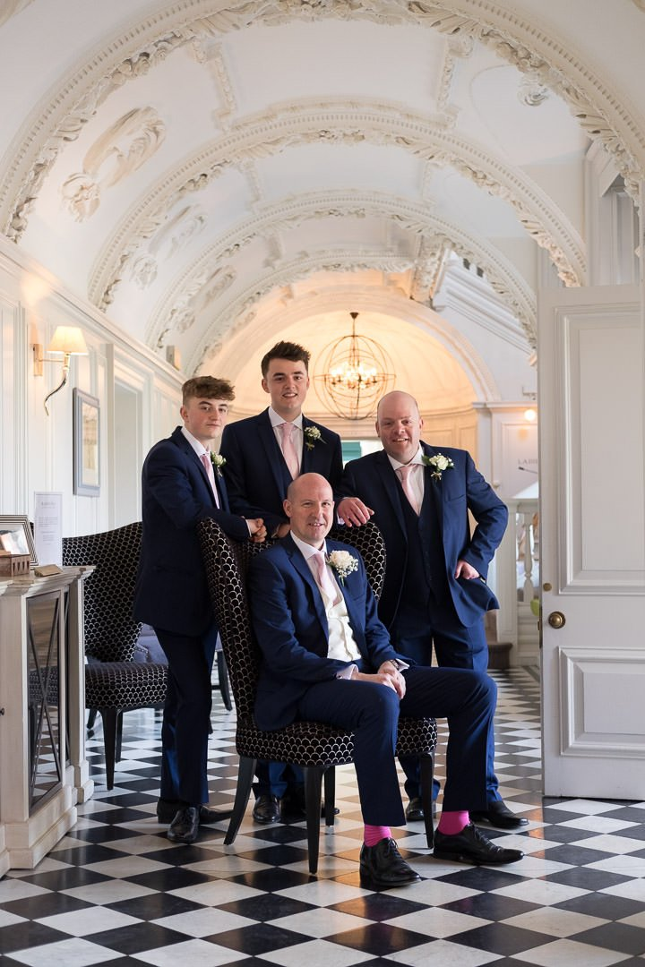 groom and groomsmen in the downstairs hall at Barnett Hill