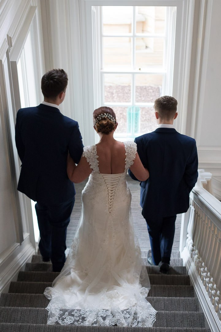 The bride is walked down the stairs by her two sons at Barnett Hill Hotel