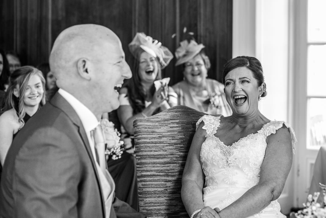 Black and white photo of the bride and groom laughing during the ceremony at Barnett Hill Hotel