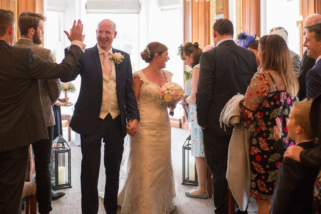 The groom high fives his brother as he walks out of the ceremony with the bride at Barnett Hill Hotel