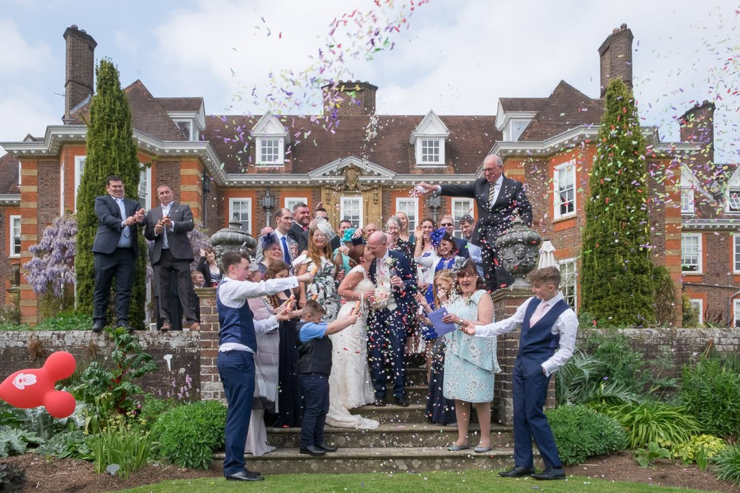 Wide shot of the bride and groom kissing surrounded by guests throwing confetti at Barnett Hill Hotel