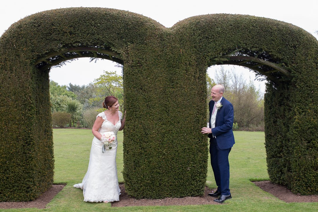 The bride and groom looking at each other under the topiary arches at Barnett Hill Hotel