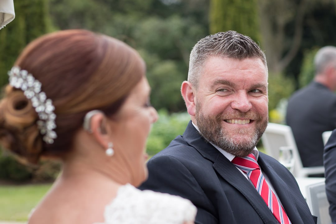 A guest smiles as the bride is talking to him at Barnett Hill Hotel