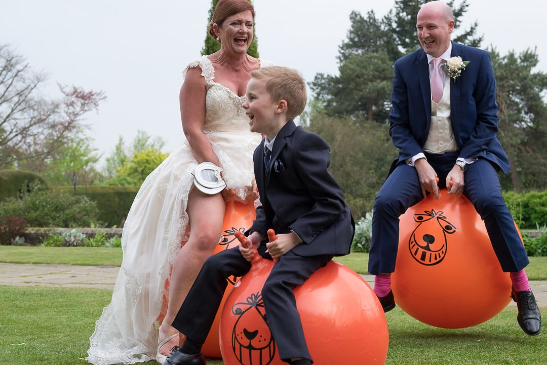 The bride, groom and young guest have fun on the space hoppers at Barnett Hill Hotel
