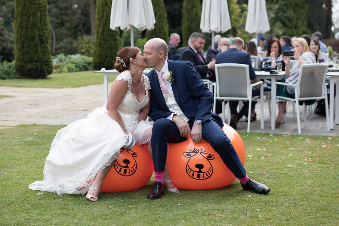 The bride and groom enjoy a kiss on the space hoppers at Barnett Hill hotel