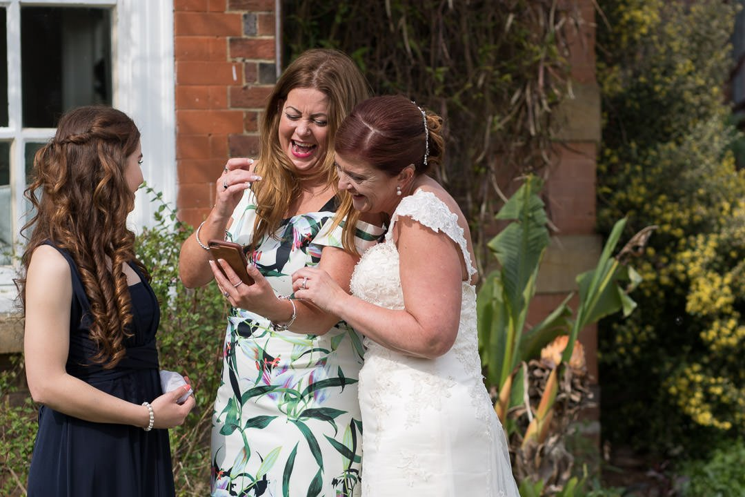 The bride laughs at a joke with her sister and niece at Barnett Hill Hotel