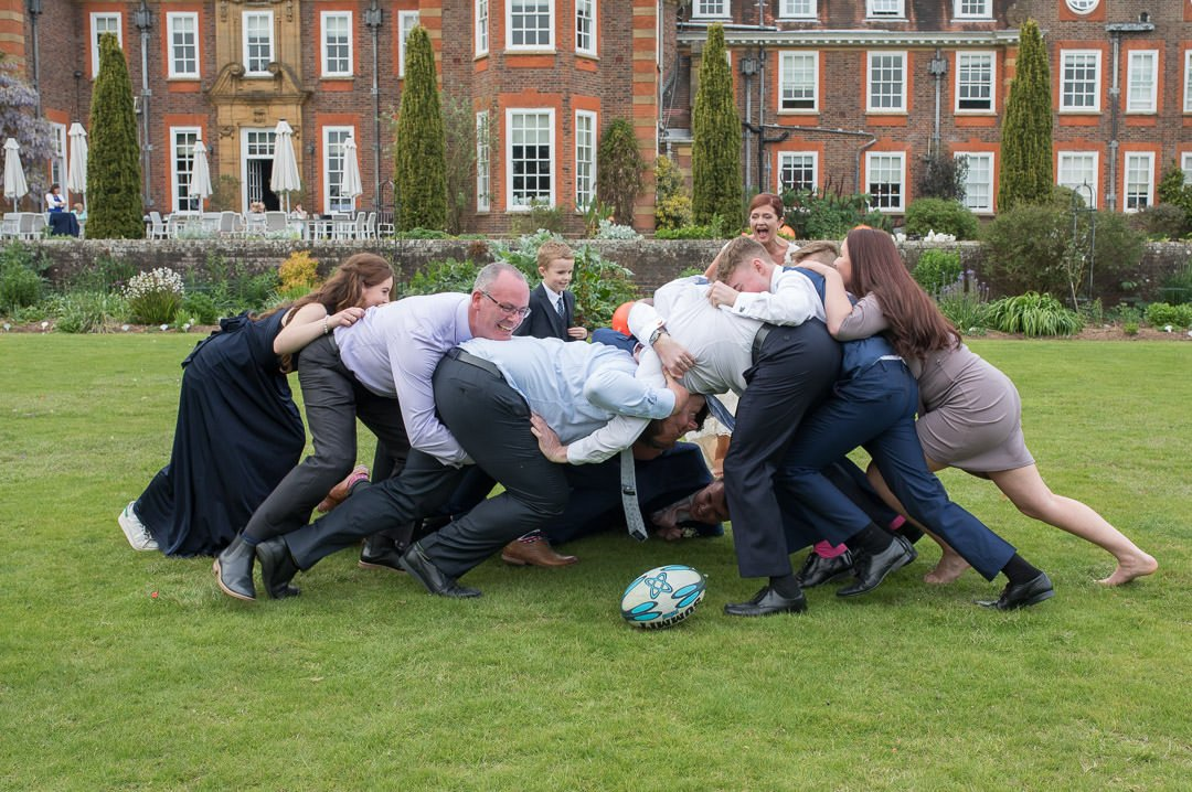 The wedding guests play rugby on the lawn at Barnett Hill Hotel