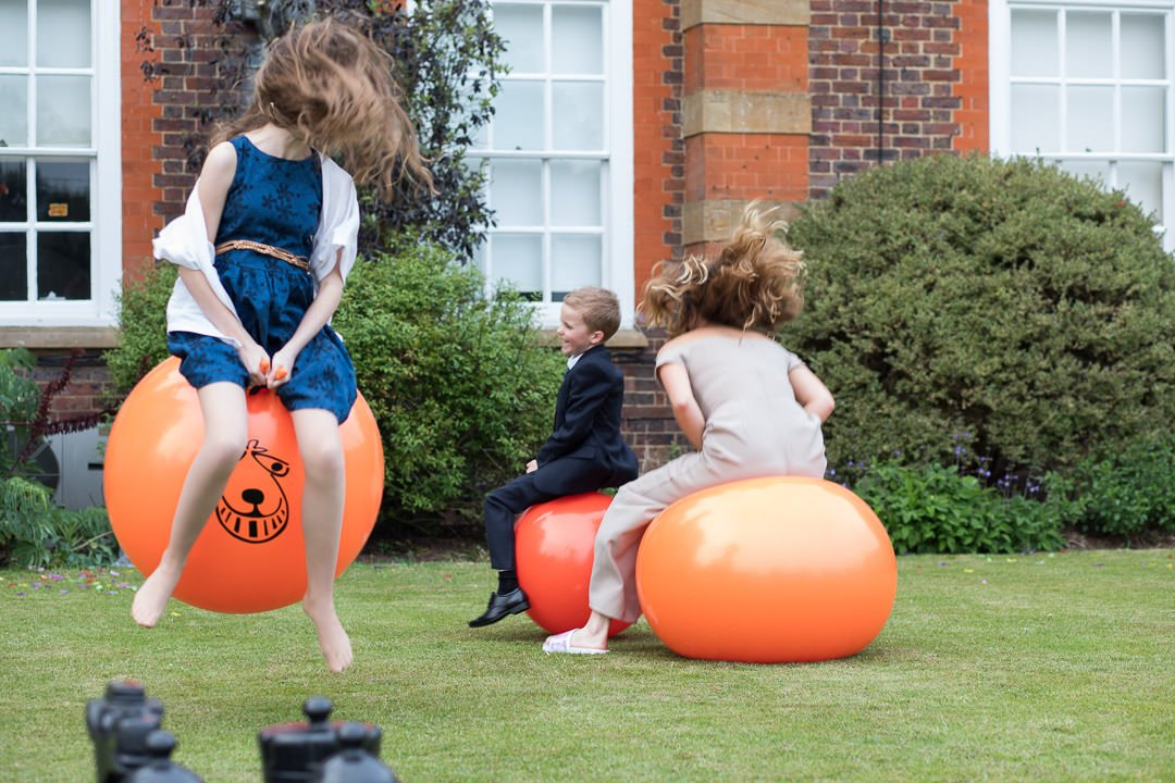 Young wedding guests have fun on the space hoppers at Barnett Hill hotel