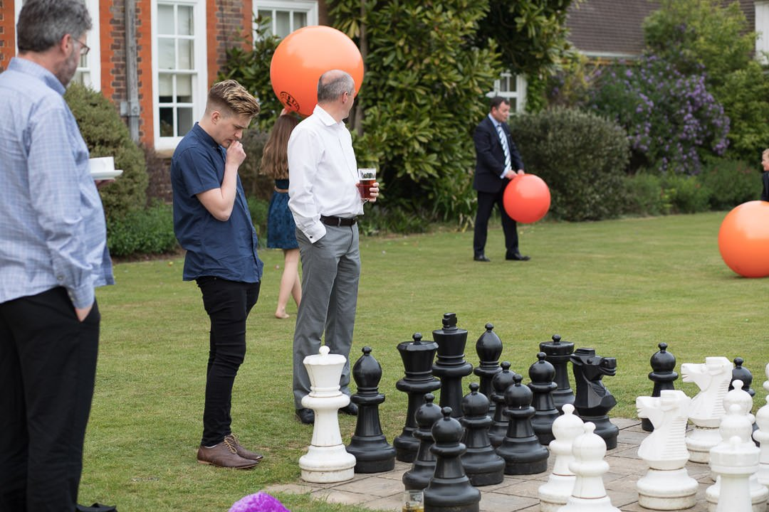 Wedding guests enjoy a game of giant chess on the patio at Barnett Hill Hotel