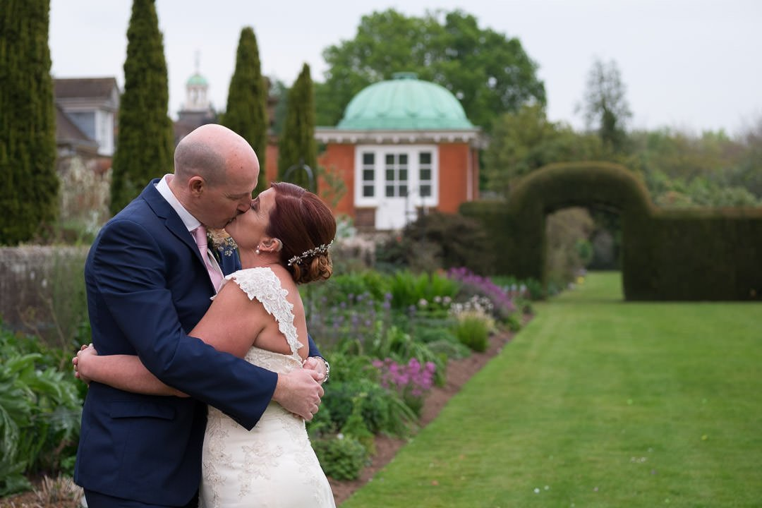 The bride and groom kiss by the flower beds at Barnett Hill hotel