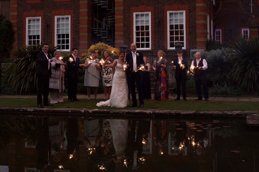 The bride and groom and wedding guests play with sparklers by the pond at Barnett Hill hotel