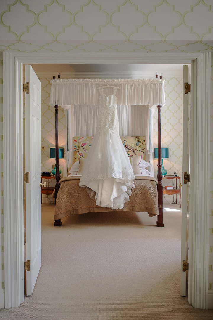 photograph of wedding dress hanging up in the bedroom at the Vineyard in Stockcross, wedding venue near Newbury in Berkshire