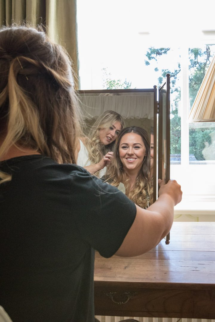 The bride looks in the mirror as she is having her hair done during bridal preparation at the Vineyard in Stockcross, wedding venue near Newbury in Berkshire