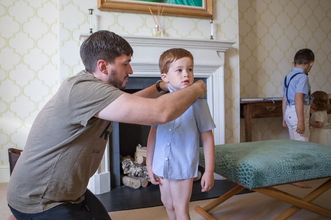 photograph of the groom helping his son during bridal preparation at the Vineyard in Stockcross, wedding venue near Newbury in Berkshire