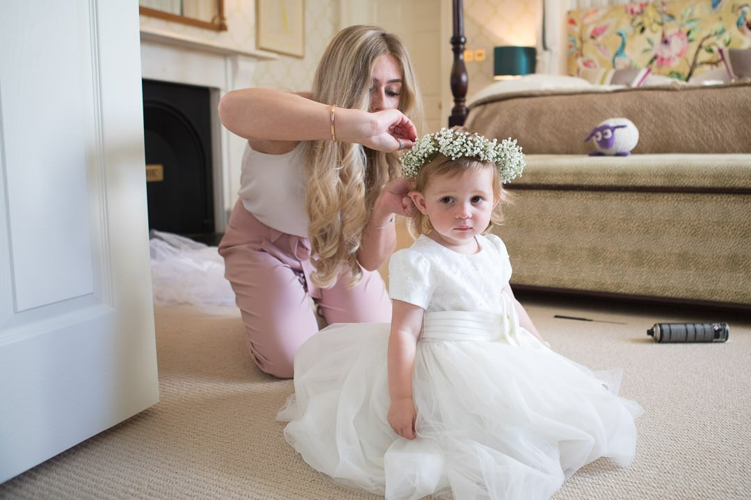 flower girl has her flower crown put on during bridal preparation at the Vineyard in Stockcross, wedding venue near Newbury in Berkshire