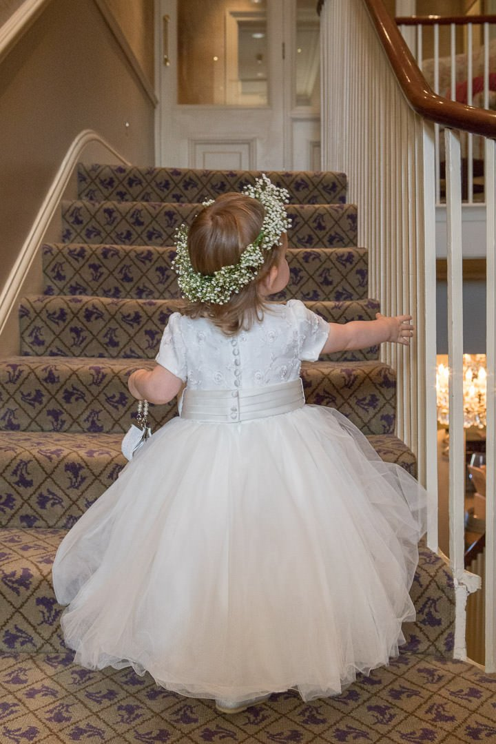 flower girl plays on the stairs at The Vineyard in Stockcross, near Newbury in Hampshire