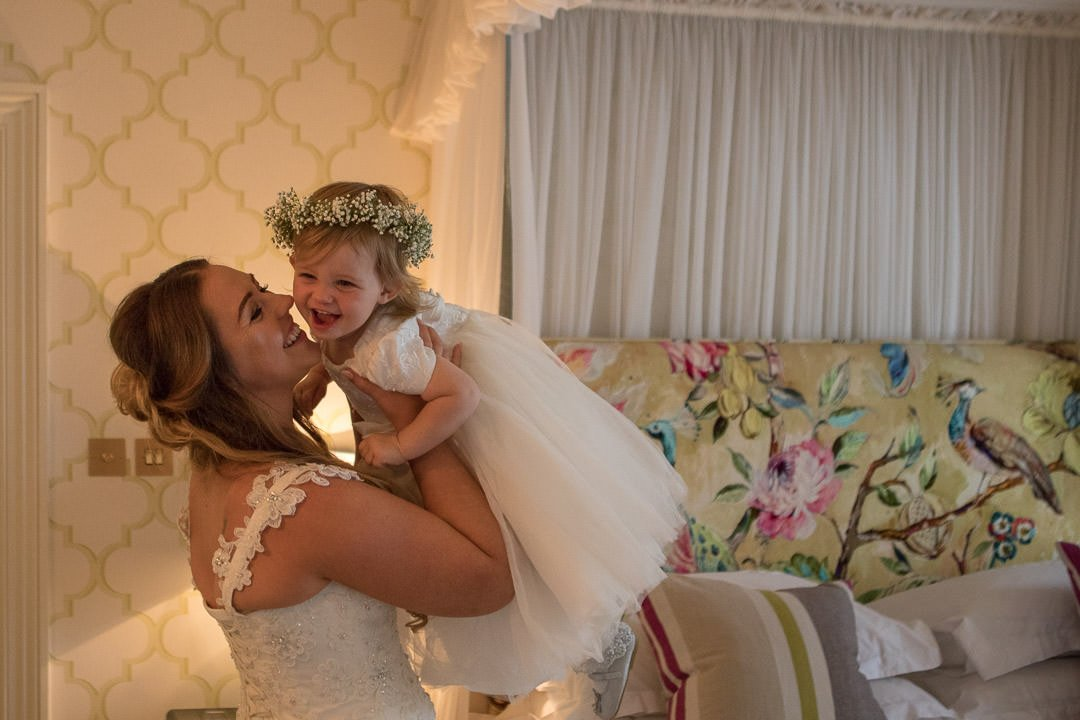 flower girl jumps into the bride's arms at the Vineyard in Stockcross near Newbury in Berkshire