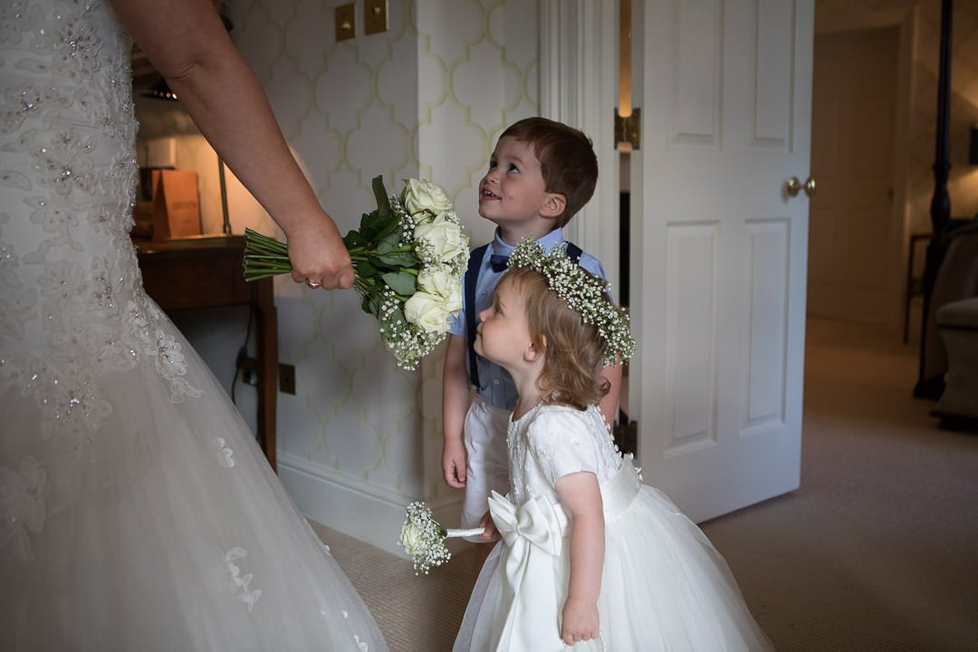 flower girl and page boy smell the bride's flowers at the Vineyard in Stockcross near Newbury in Berkshire