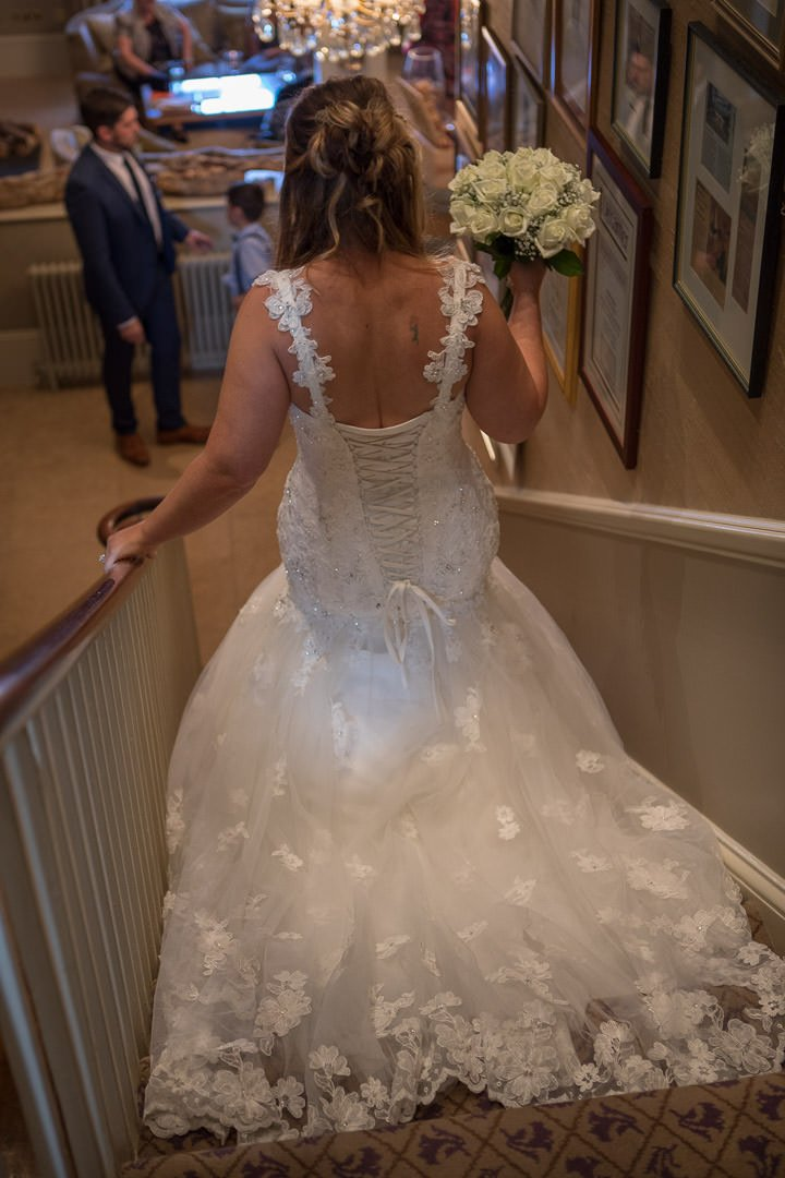 The bride goes downstairs at The Vineyard in stockcross near Newbury