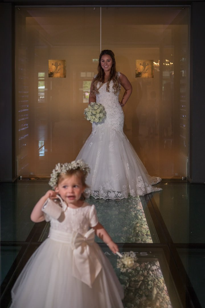 The flower girl photobombs the bridal portrait in the wine cellar at the Vineyard, near Newbury