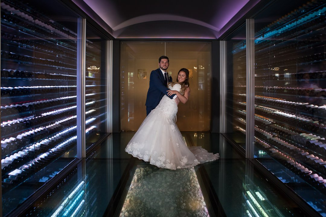 The bride and groom pose in the wine cellar at the Vineyard near Newbury in Berkshire