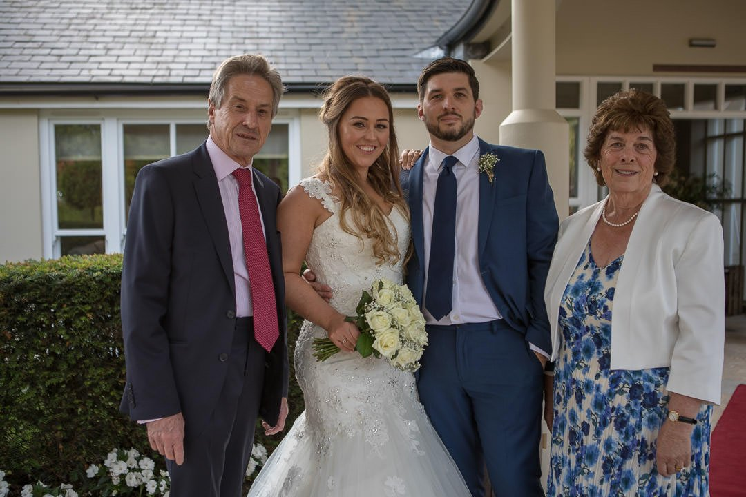 The bride and groom pose with parents outside the front door at the Vineyard near Newbury in Berkshire
