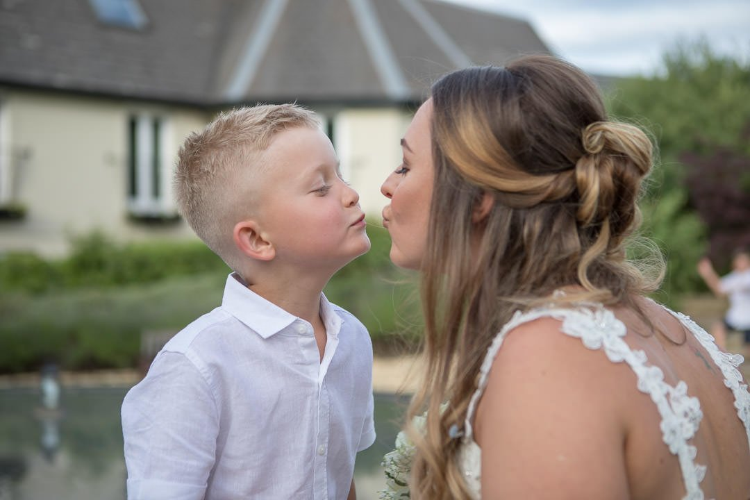 The bride air kisses a young guest at the Vineyard near Newbury in Berkshire