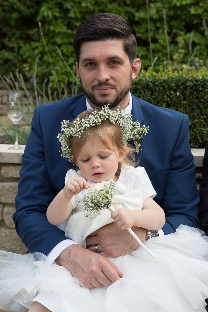 The groom sits with his young daughter on his knee at the Vineyard near Newbury in Berkshire