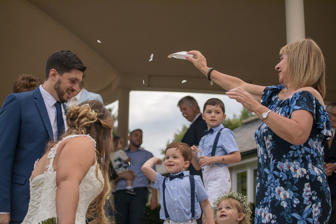 young guests enjoy throwing confetti at the bride and groom at the Vineyard near Newbury