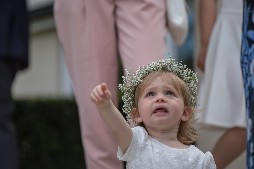 Flower girl points into the sky at the Vineyard