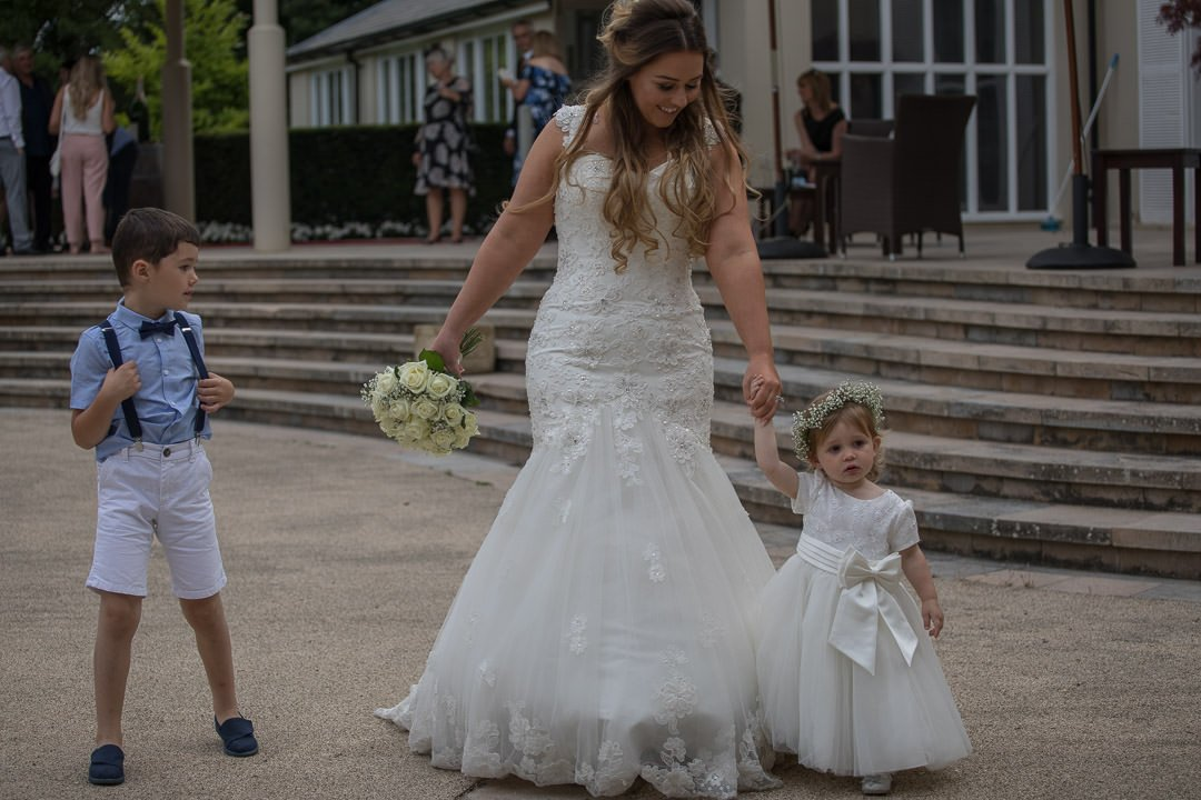 The bride and little flower girl go for a walk at the Vineyard