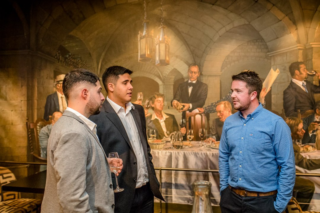 male wedding guests chat by the mural at the Vineyard near Newbury in Berkshire