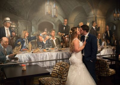 The bride and groom kiss by the mural at the Vineyard near Newbury in Berkshire