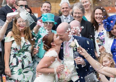laughing bride and groom kiss as guests throw confetti at Barnett Hill Hotel in Surrey-0001