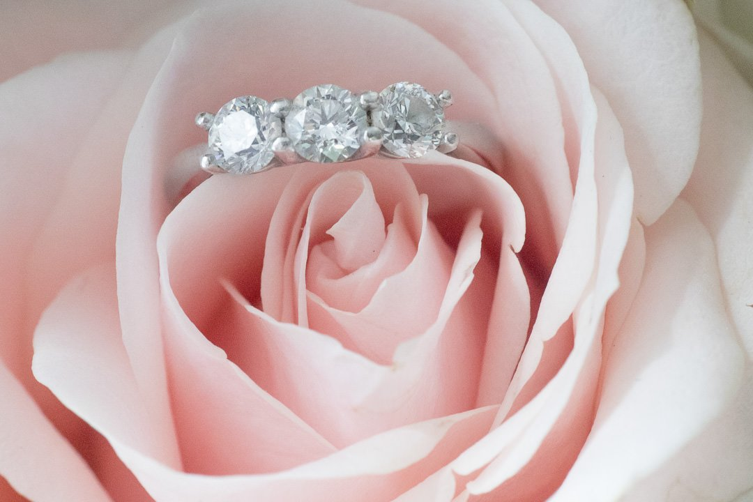 three stone diamond engagement ring in pink rose wedding flowers photographed by surrey wedding photographer
