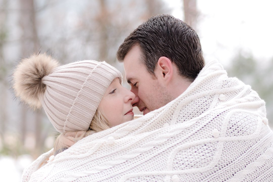 engaged couple hug under a white blanket in the snow at Swinley forest