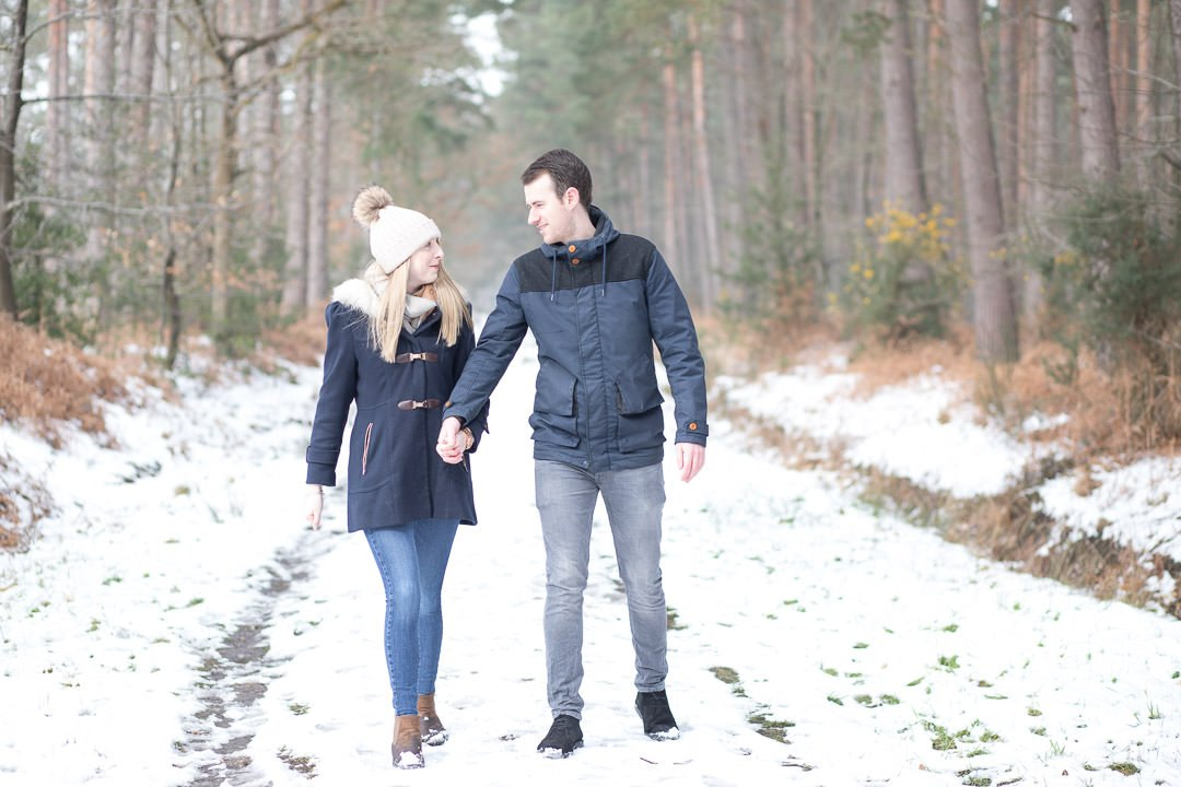 engaged couple walking in the snow and holding hands, in Swinley forest