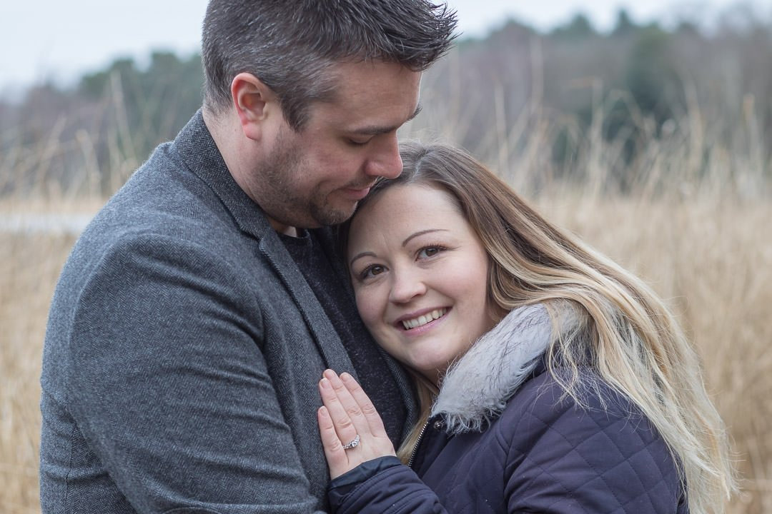 engaged couple embrace during their autumn engagement photo session at Virginia Water