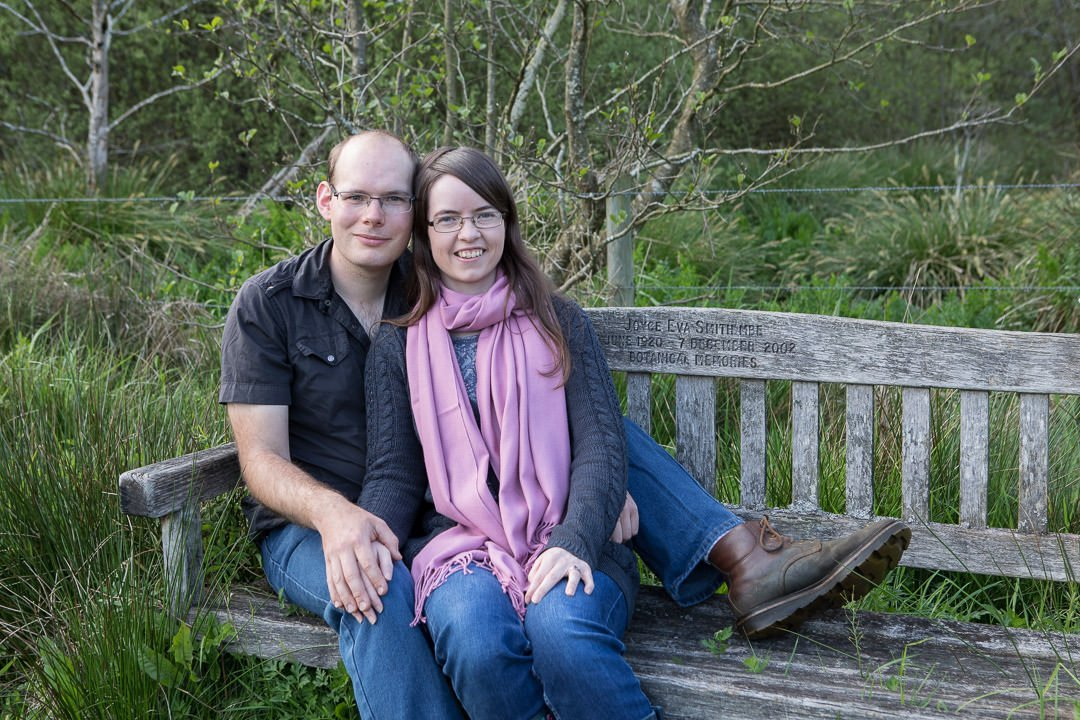 engaged couple sit together during their engagement photo session at Thundry meadows, near Elstead