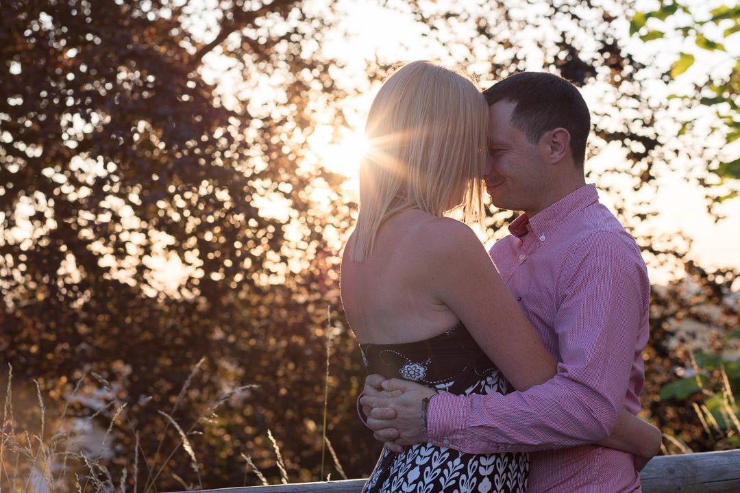 engaged couple hug and embrace by a beech tree as the sun sets at Guildford castle