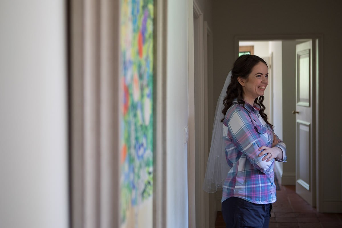 smiling bride waits in the corridor by a painting