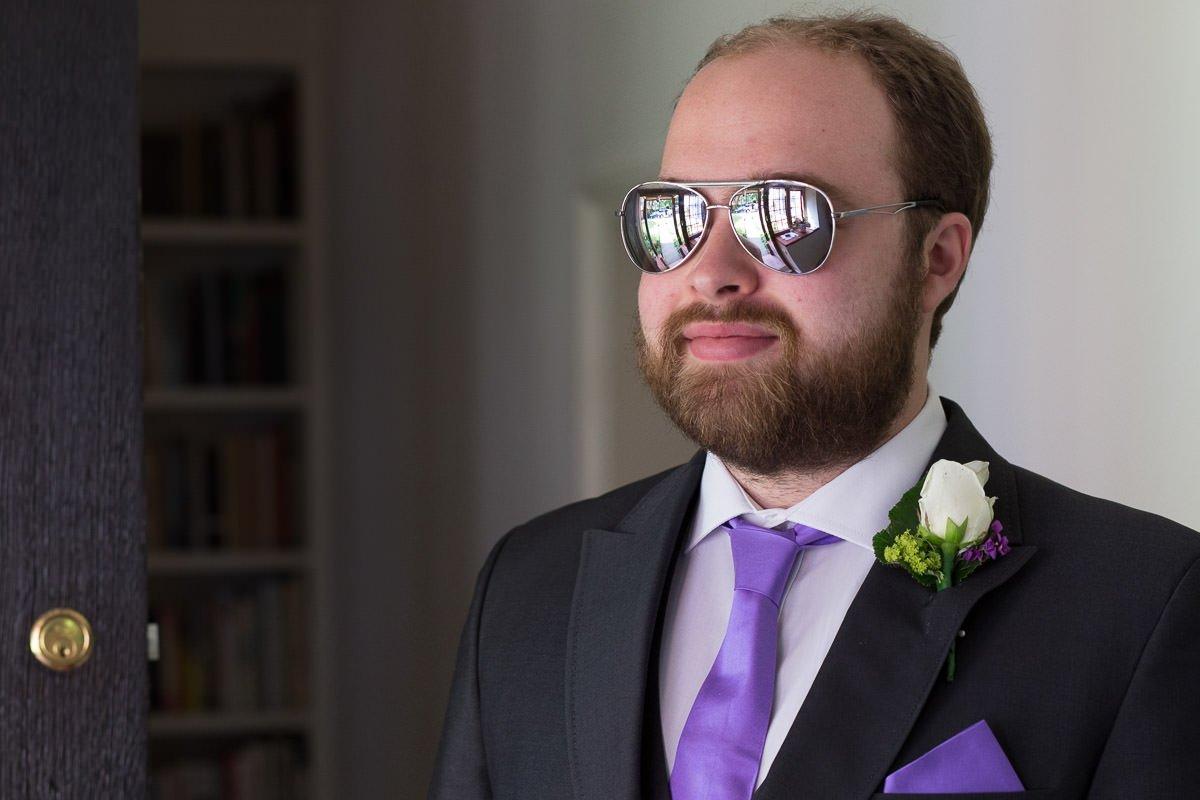 Building reflected in groomsman's sunglasses
