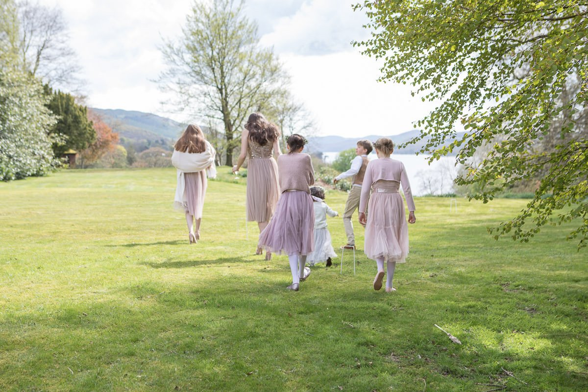 very English scene of bridesmaids walking together across the lawn with the Lake district behind