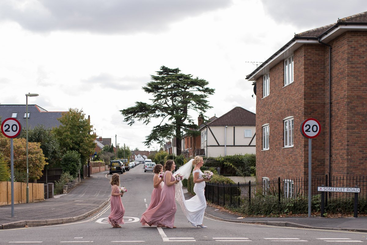 Bride and bridesmaids cross the street as they walk to church